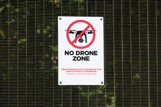 No drone zone sign not allowing flying of quadcopter at military police site near airport